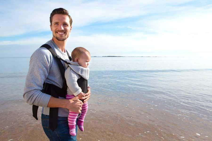 папа держит малыша в кенгуру
