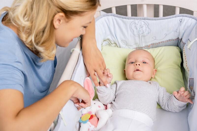 малыш в кроватке с бортиками для детской кроватки