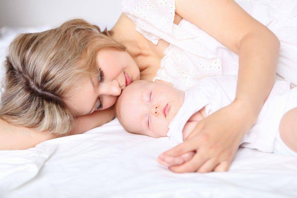Молодая мама с младенцем спят на кровати