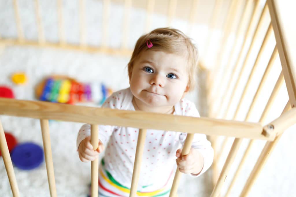 Маленькая девочка стоит в игровом манеже