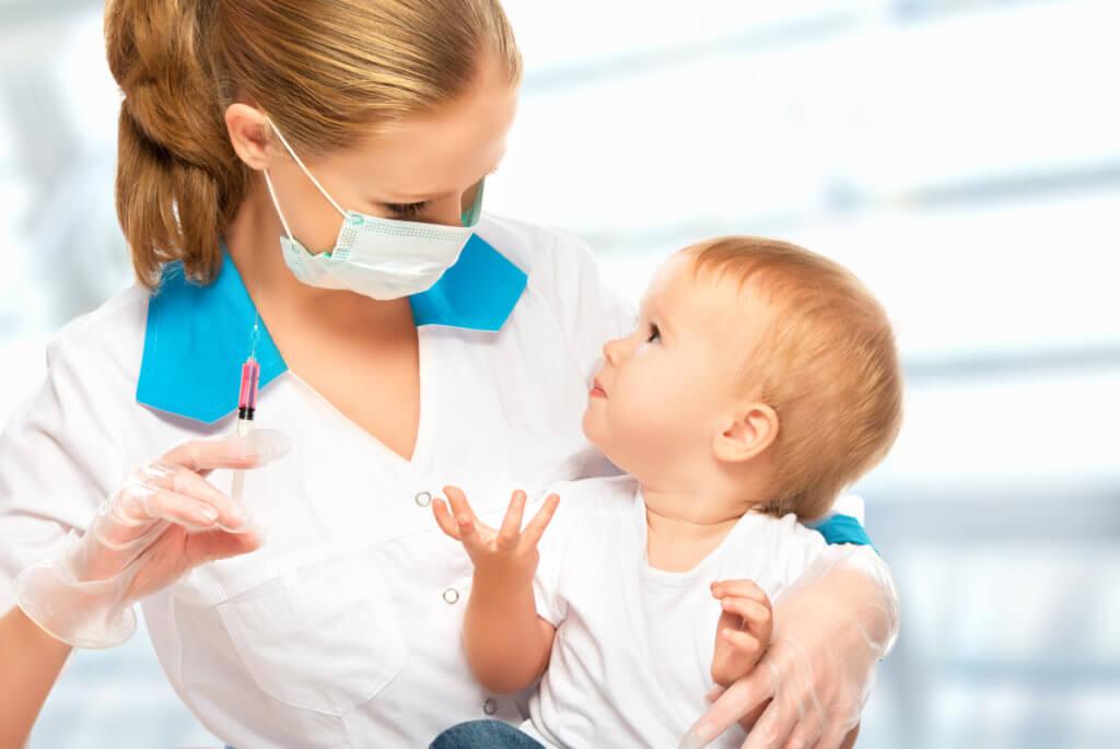 Врач проводит вакцинацию делает прививку маленькому ребенку