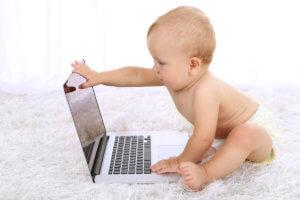 Маленький ребенок сидит перед ноутбуком