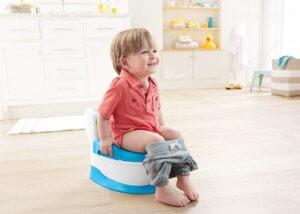 Маленький мальчик учится сидеть на горшке