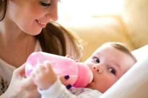 мама кормит из бутылочки ребенка